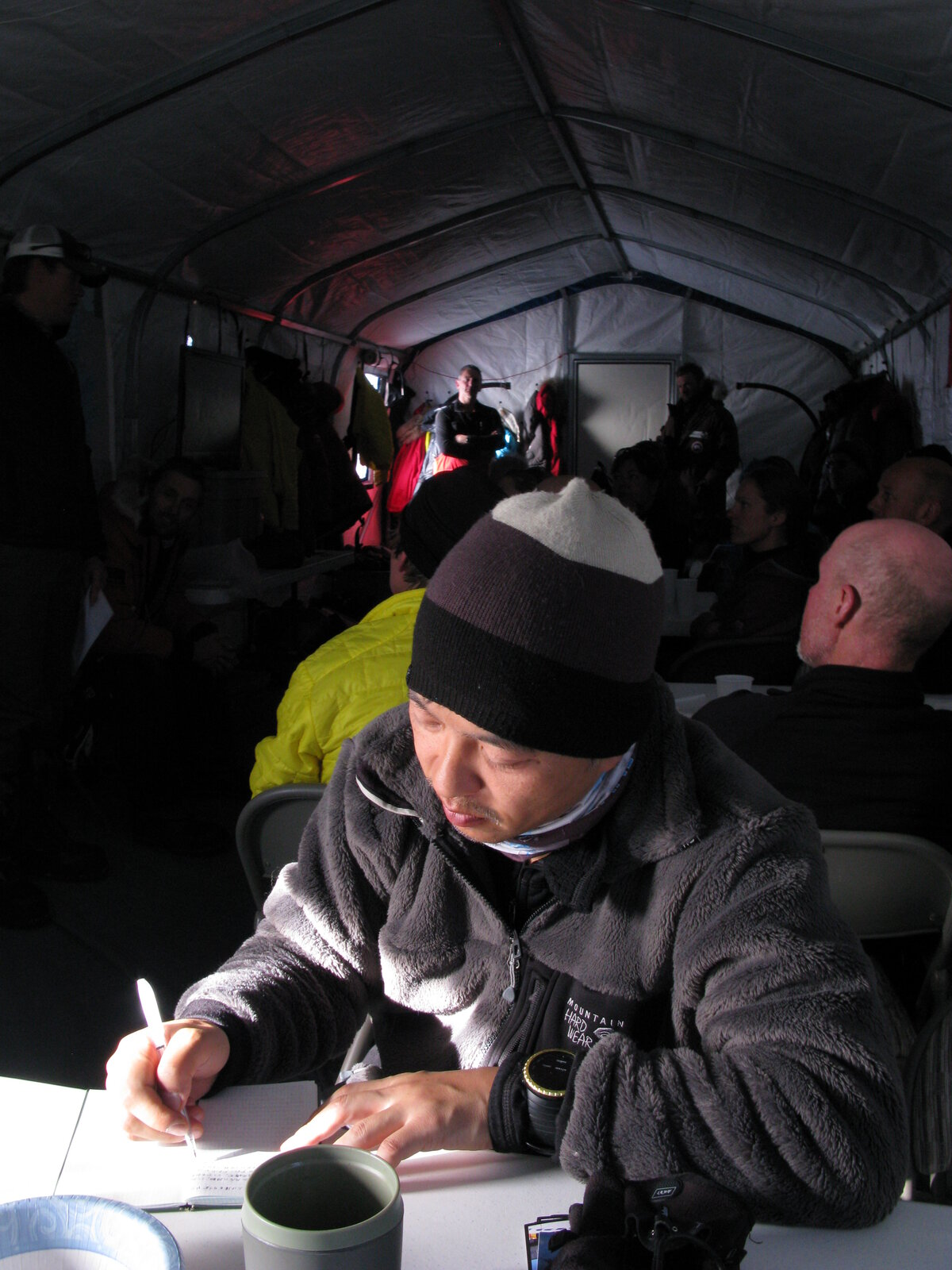 Guests journals inside dining tent at ALE's South Pole Camp