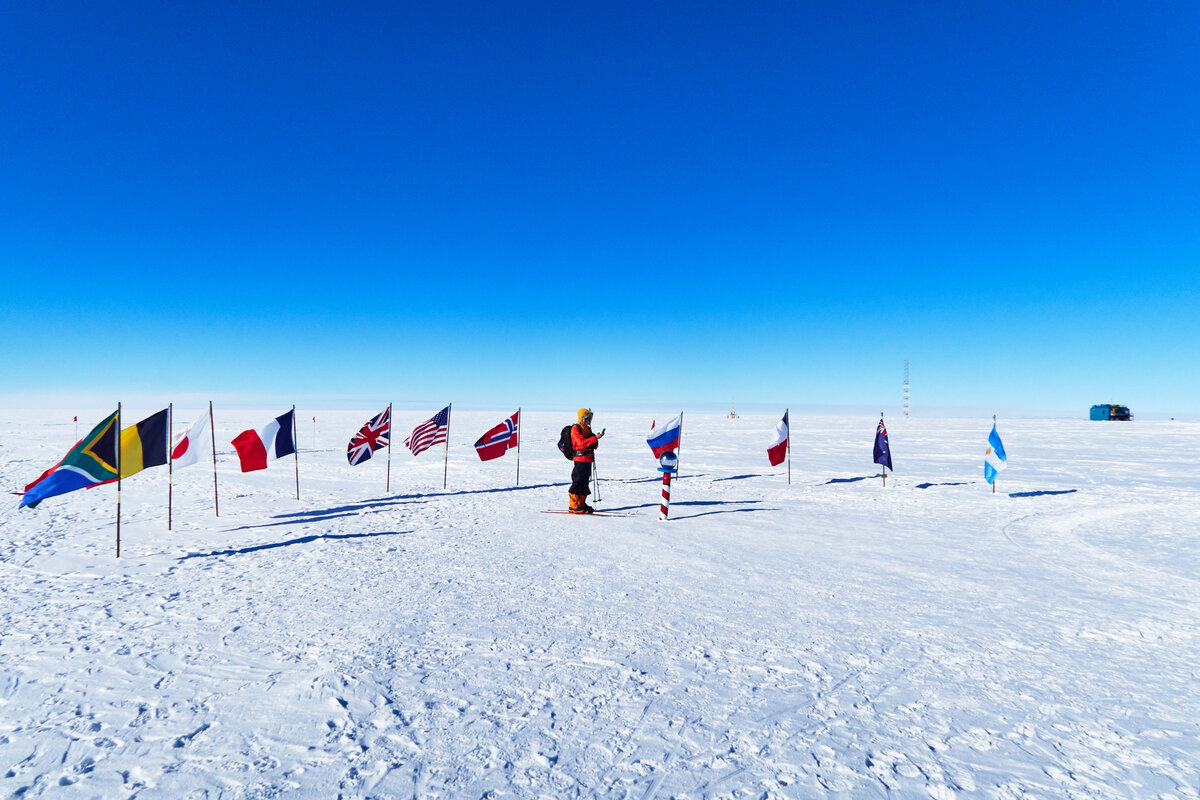 Skier surrounded by flags of Antarctic Treaty nations