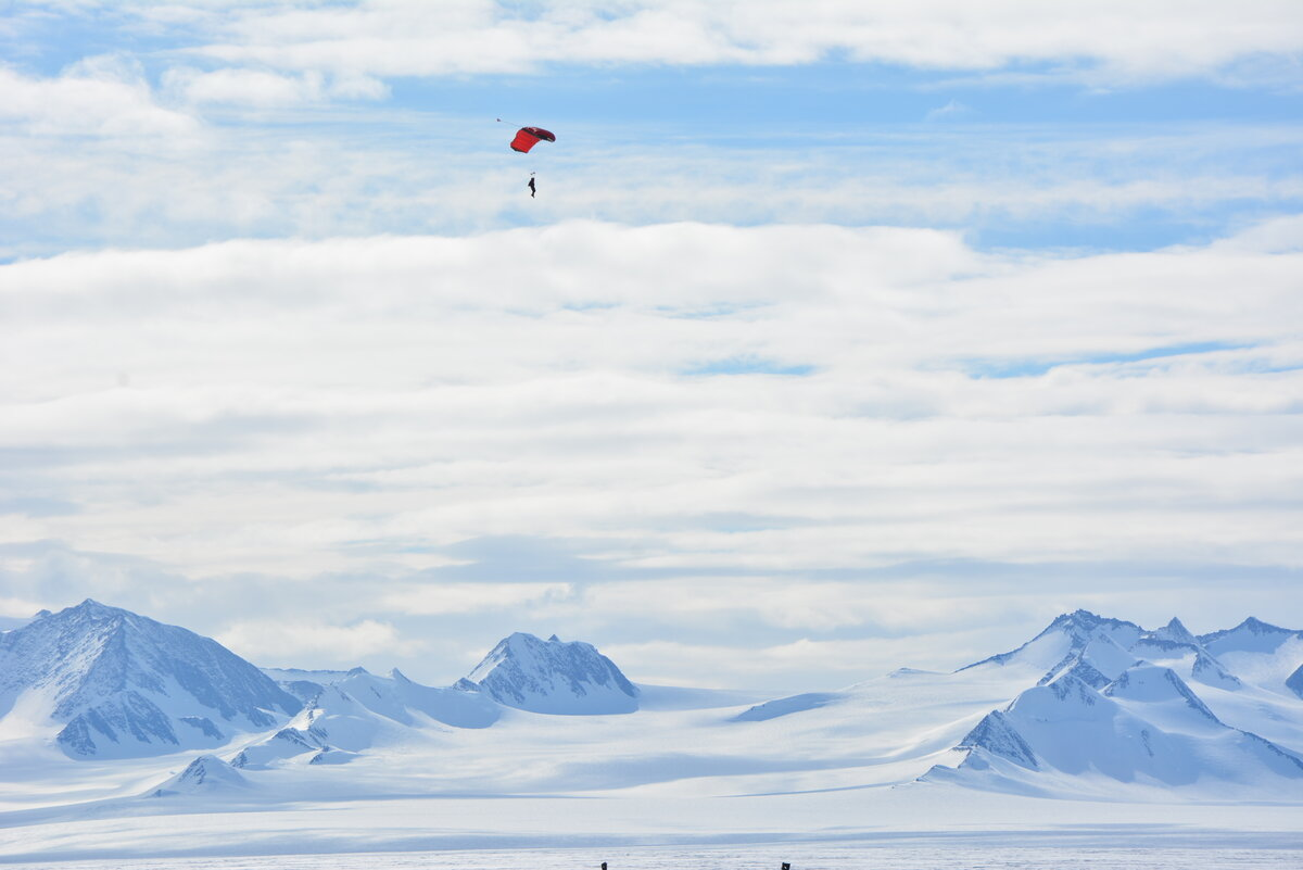 A skydiver steers their parachute towards the landing area