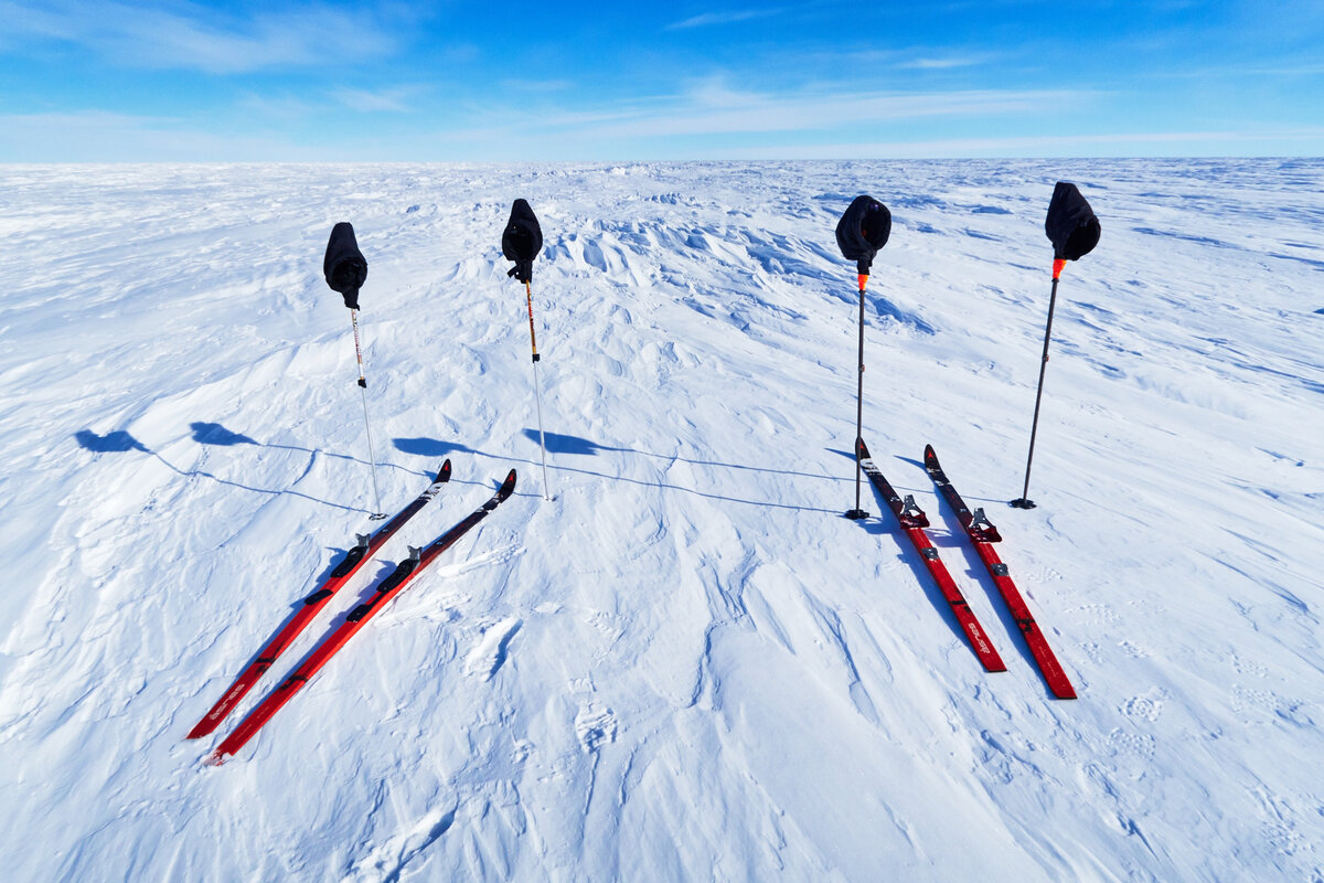 Two sets of skis, poles, and pogies await their skiers