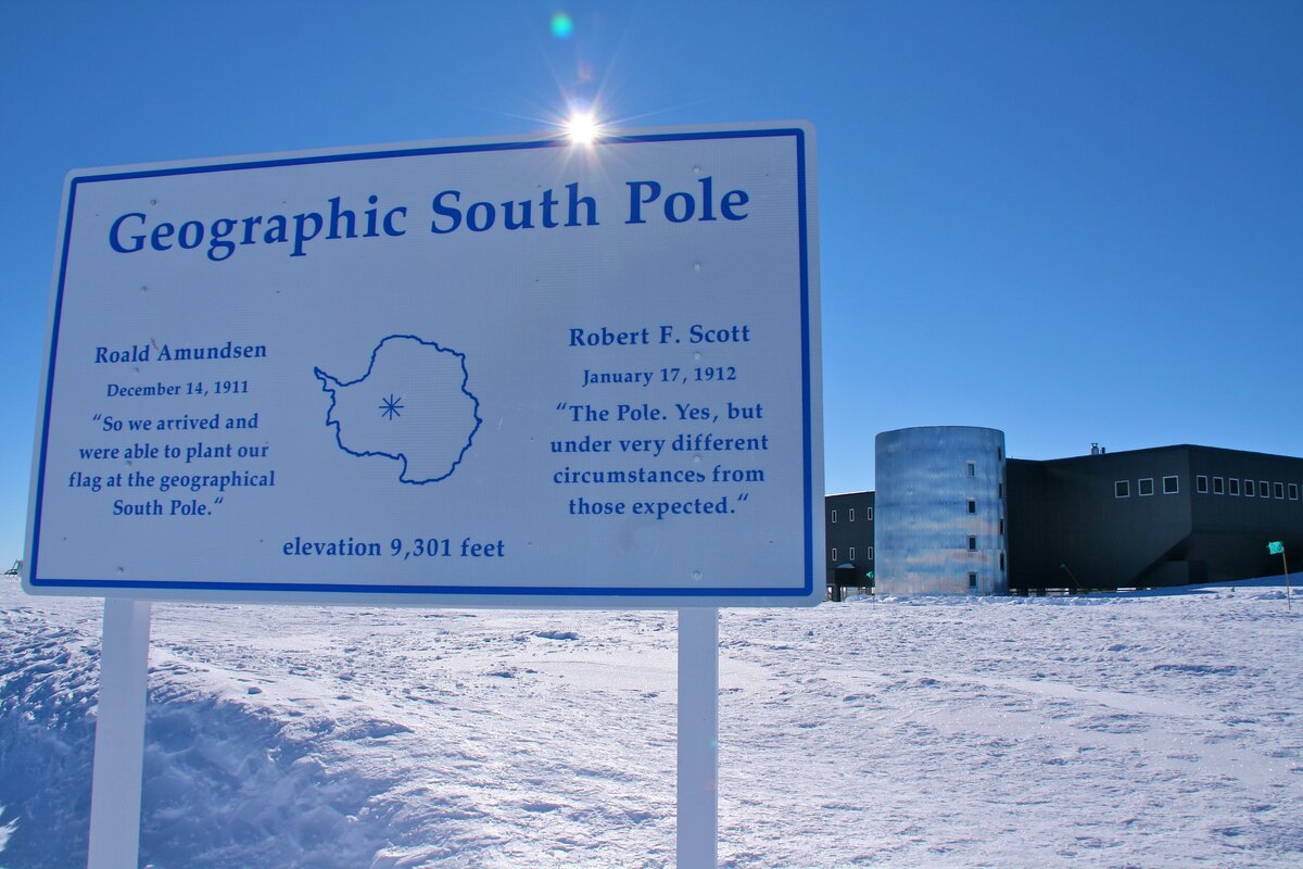 Geographic South Pole Sign with station in background