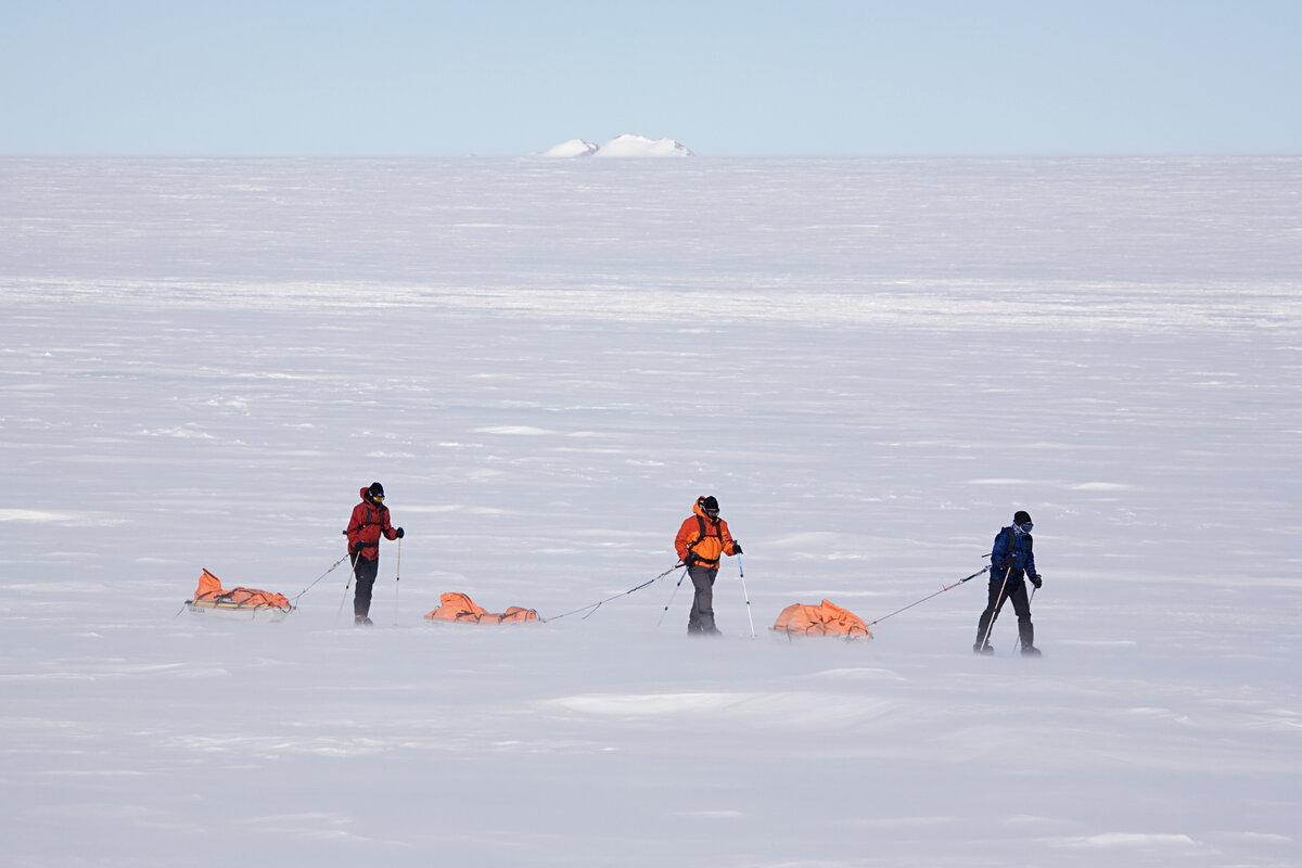Team hauls sleds across an empty white landscape