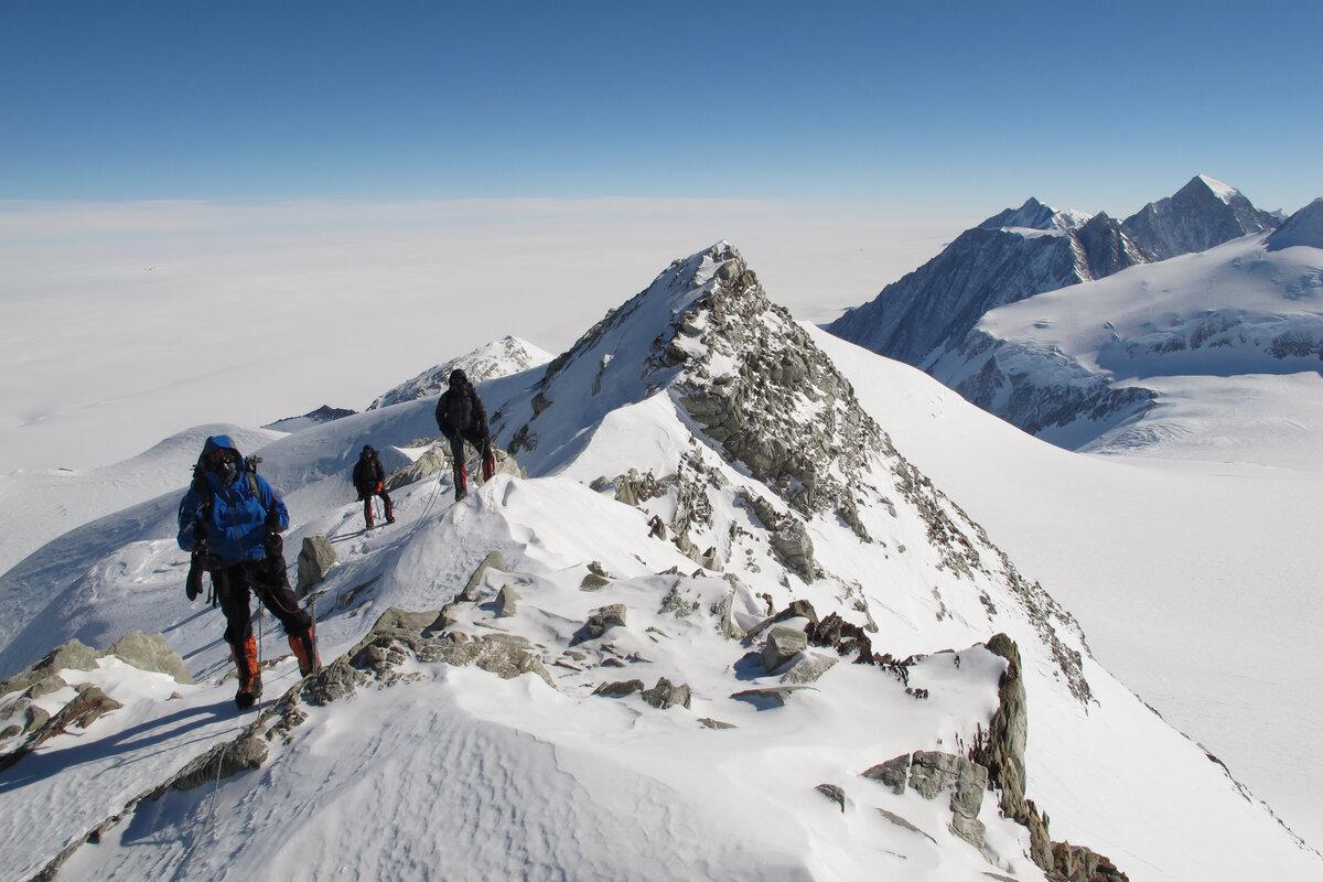 Climbers work their way along the rocky summit ridge