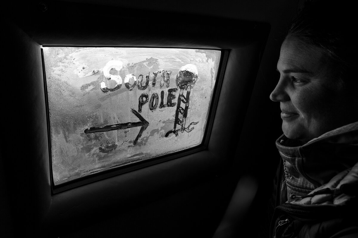 A passenger looks out the frozen window of the Basler where she has written South Pole