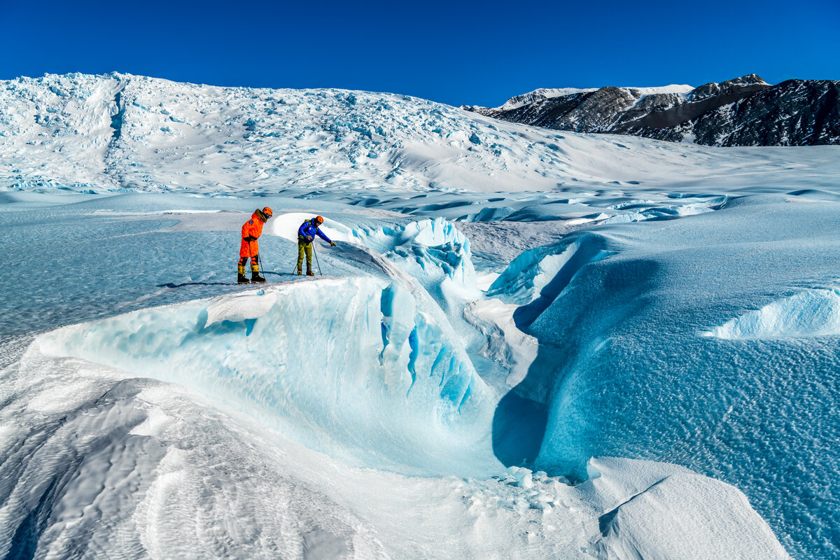 A guide points out features in the blue-ice of the Drake Icefall