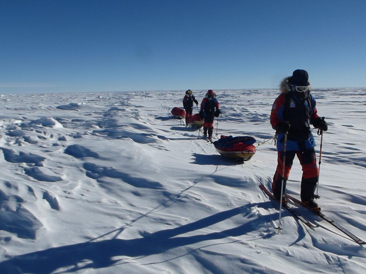 Skiers look for the easiest path through sastrugi
