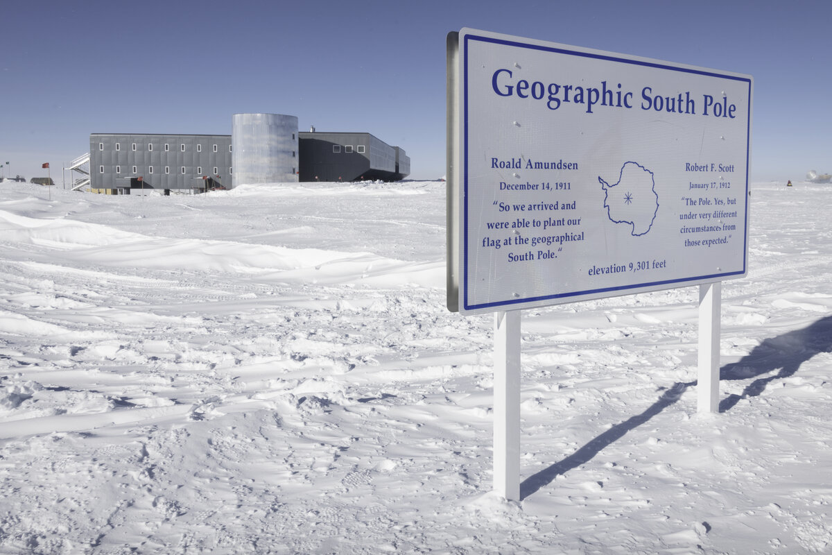 The Geographic South Pole sign with Amundsen-Scott South Pole Station in the background
