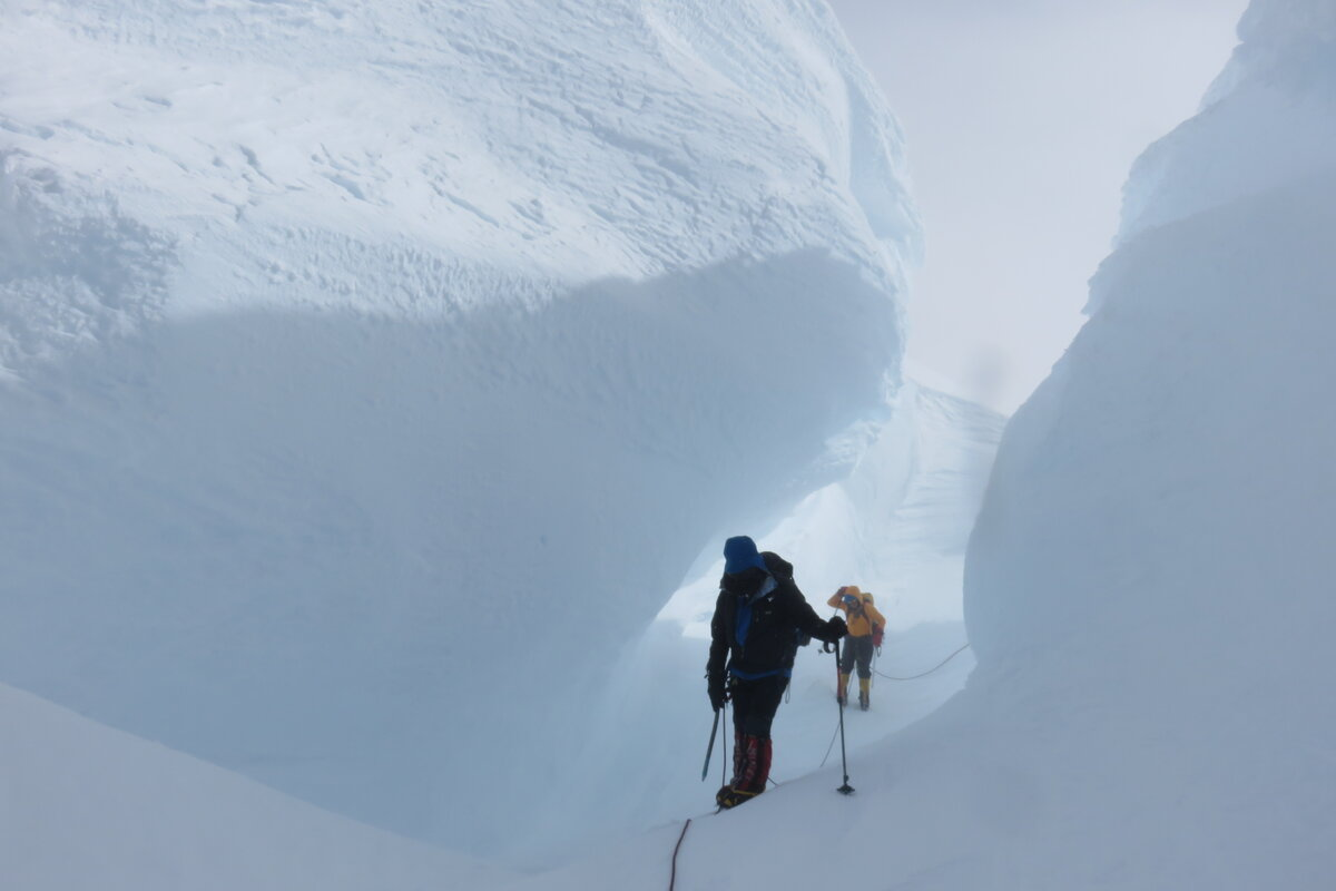 Climbers navigate through enormous snow mushrooms