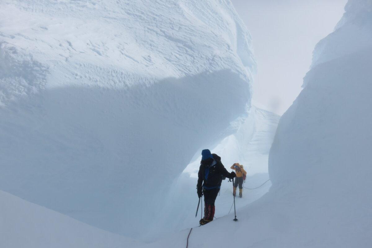 Climbers navigate through enormous snow mushrooms