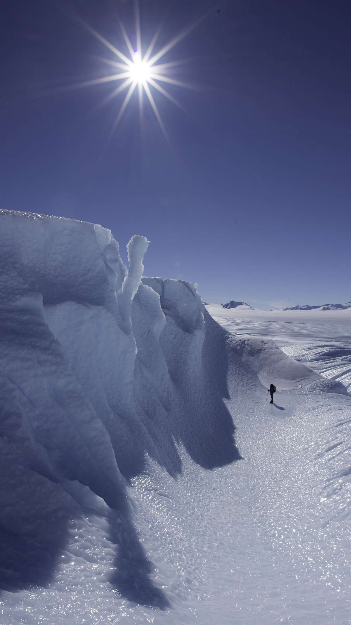 A guest walks through a blue-ice trough at the Drake Icefall