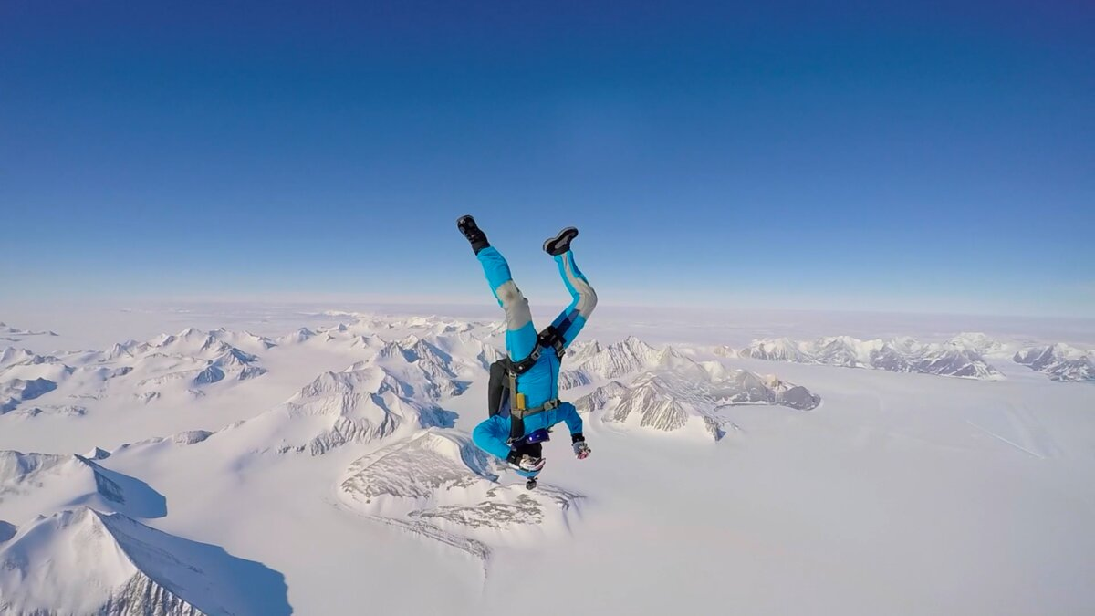 A skydiver hangs in the sky over Union Glacier